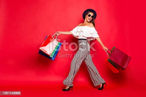 istock Full length body size portrait of careless carefree trendy stylish elegant chic lady wearing eyeglasses eyewear off-the-shoulders blouse top high heels shoes isolated on red background 1067448968