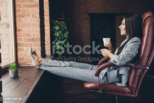 istock Full length, body, size  portrait of confident lady in gray checkered suit with cup of drink looks through window with her legs on the windowsill sit in comfort armchair on industrial workplace 1059105316