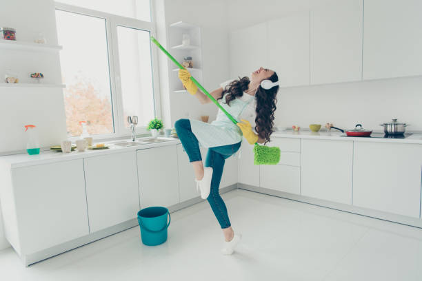 Full length body size portrait of her she nice adorable beautiful cheerful wavy-haired house-wife using broom dancing having fun in modern light white interior indoors stock photo