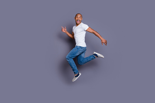 istock Full length body size portrait of his he nice cool handsome attractive masculine cheerful guy wearing white shirt jeans having fun isolated over gray violet purple pastel background 1129154077