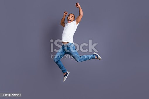925466128 istock photo Full length body size portrait of his he nice handsome attractive muscular strong cheerful cheery crazy guy in white shirt jeans having fun great cool triumph isolated over gray background 1129155229