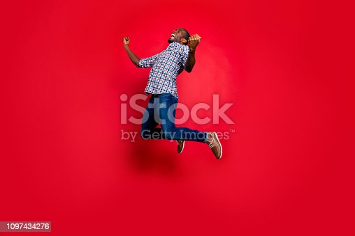 925466128 istock photo Full length body size portrait of nice funny glad handsome cheerful positive trendy guy wearing checkered shirt showing winning gesture cool party in air isolated on bright vivid shine red background 1097434276