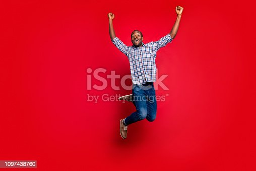 925466128 istock photo Full length body size portrait of nice funny glad handsome cheerful optimistic positive guy wearing checkered shirt raising hands up party in air isolated on bright vivid shine red background 1097438760