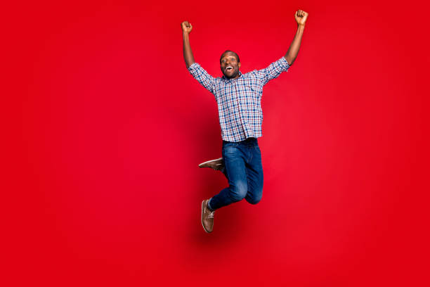 Full length body size portrait of nice funny glad handsome cheerful optimistic positive guy wearing checkered shirt raising hands up party in air isolated on bright vivid shine red background Full length body size portrait of nice funny glad handsome cheerful optimistic positive guy wearing checkered shirt raising hands up party in air isolated on bright vivid shine red background jump shot stock pictures, royalty-free photos & images