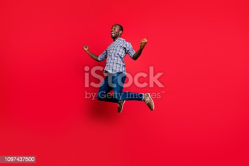 925466128 istock photo Full length body size portrait of nice funny handsome cheerful positive guy wearing checkered shirt showing winning gesture party in air isolated on bright vivid shine red background 1097437500