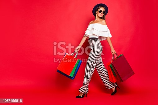 istock Full length body size portrait of trendy stylish elegant chic lady wearing eyeglasses eyewear off-the-shoulders blouse top high heels shoes with colorful bags leisure isolated on red pastel background 1067455816