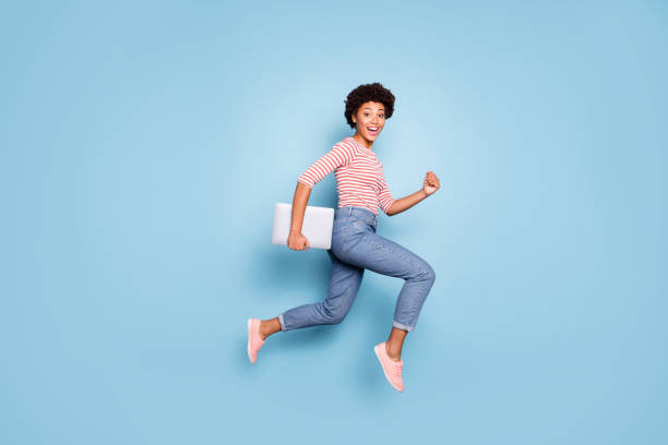 Full length body size profile side photo of excited crazy cheerful positive nice pretty sweet youngster wearing jeans denim striped shirt footwear isolated blue pastel color background stock photo