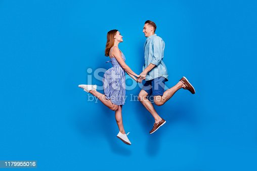 Full length body size profile side view of her she his he two nice attractive, dreamy cheerful glad partners holding hand jumping having fun isolated on bright vivid shine vibrant blue color background