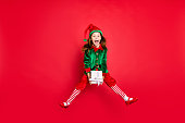 istock Full length body size profile side view of nice attractive cheerful positive overjoyed glad funny small little pre-teen elf holding in hands white box isolated over bright vivid shine red background 1173844135
