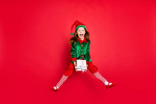 ganzer körper größe profil seitenansicht von schönen attraktiven positiven positiv überglücklich frohe lustige lustige kleine pre-teen elfe halten in den händen weiße box isoliert über hell leuchtenden leuchtenden roten hintergrund - nikolaus kostüm stock-fotos und bilder