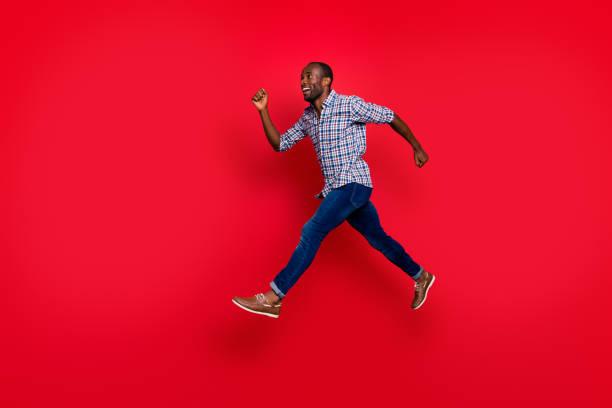 voller länge körper größe profil seitenansicht schön süß gut aussehend attraktive fröhlich positive sportliche mann trägt kariertes hemd laufen in luft zum ziel auf hellen lebhaften glanz rot hintergrund isoliert - druck jeans stock-fotos und bilder