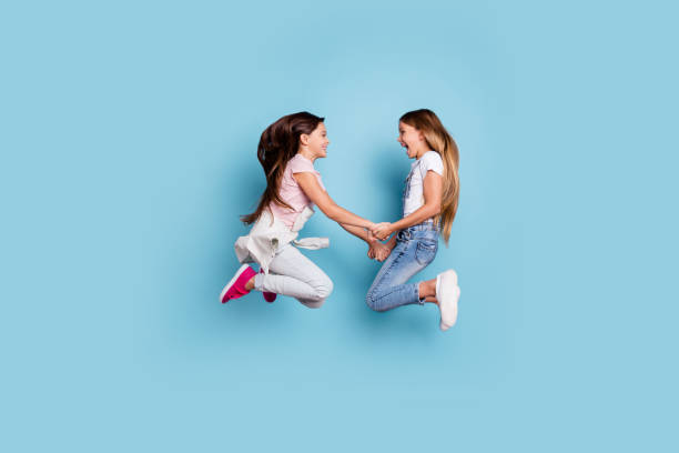 Full length body size profile side view of two people nice cute attractive cheerful straight-haired pre-teen girls having fun great weekend holding hands isolated over blue pastel background Full length body size profile side view of two people nice cute attractive cheerful straight-haired pre-teen girls having fun great weekend holding hands isolated over blue pastel background jump shot stock pictures, royalty-free photos & images