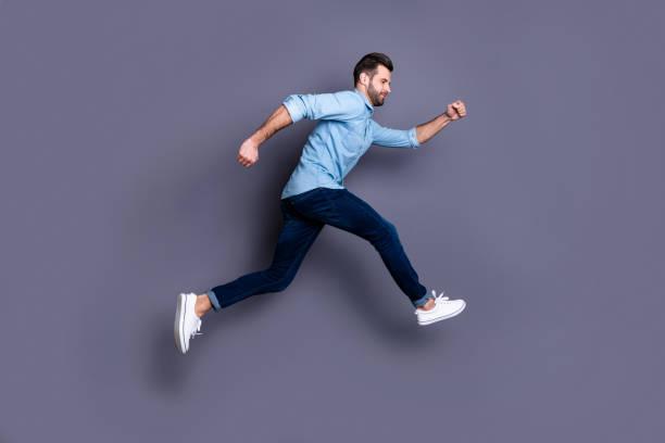 ganzer körper größe profil seite ansicht porträt von seinem er schön aussehende attraktive fröhliche kerl mit spaß laufen schnell isoliert über grau violett lila pastell hintergrund - druck jeans stock-fotos und bilder