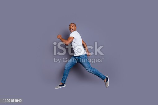 925466128 istock photo Full length body size profile side view portrait of his he nice handsome attractive masculine cheerful guy in white shirt jeans having fun running away isolated over gray pastel background 1129154842