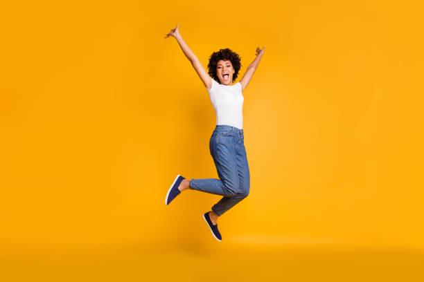 completo comprimento corpo tamanho lado perfil foto jumping alta bonita ela sua senhora mãos braços para cima ganhar jogo jogar match vestindo casual jeans denim branco t-shirt roupas isoladas amarelo brilhante vivid fundo - excitação - fotografias e filmes do acervo