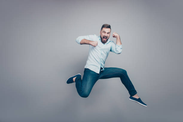 Full length body size studio photo portrait of excited cheerful handsome guy jumping up looking at camera isolated grey background Full length body size studio photo portrait of excited cheerful handsome guy jumping up looking at camera isolated grey background jump shot stock pictures, royalty-free photos & images