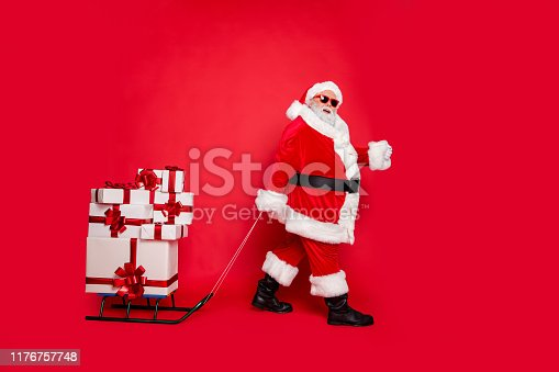 Full length body size view of generous kind funky fat overweight plump, gray-haired bearded man carrying many pile stack cool purchases winter tradition isolated over bright vivid shine red background