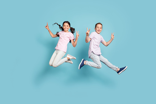 Full length body size view of her she his he nice attractive small little cheerful cheery, friends friendship kids jumping showing v-sign having fun isolated over blue pastel color background