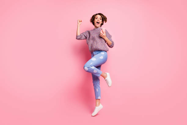 Full length body size view of her she nice attractive lovely pretty overjoyed cheerful cheery glad excited brown-haired girl using cell jumping great news isolated over pink pastel color background stock photo