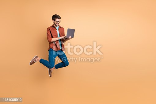 istock Full length body size view of his he nice attractive cheerful cheery successful brunet guy jumping in air using laptop home-based job isolated over beige color pastel background 1181005910