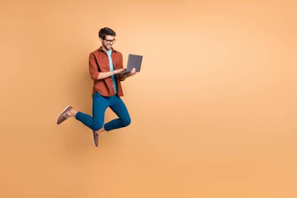 Vista de tamaño del cuerpo de longitud completa de su agradable alegre alegre alegre exitoso brunet chico saltando en el aire usando el trabajo casero portátil aislado sobre el fondo pastel de color beige - foto de stock