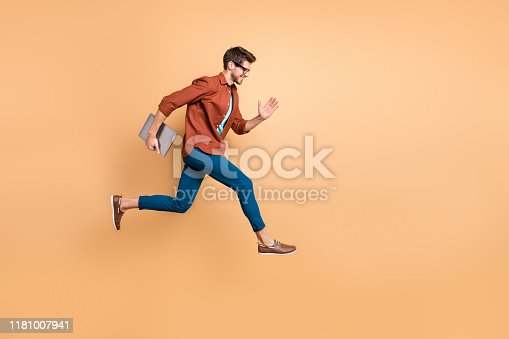Full length body size view of his he nice attractive cheerful cheery successful brunet, guy jumping in air carrying laptop running fast late hurry-up isolated over beige color pastel background