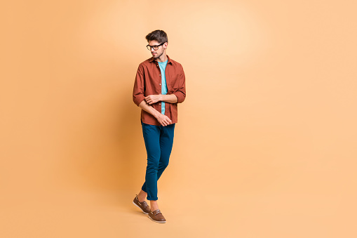istock Full length body size view of his he nice attractive fashionable content brunet guy partner hipster walking fixing sleeve isolated over beige color pastel background 1181006025