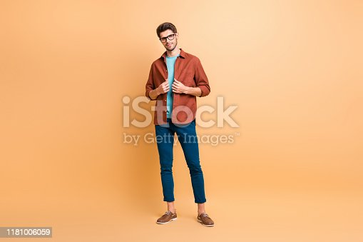 istock Full length body size view of his he nice attractive lovely fashionable brunet guy dandy fixing clothing shirt posing new cool modern look isolated over beige color pastel background 1181006059
