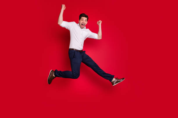 Full length body size view of his he nice attractive lovely cheerful cheery content overjoyed guy having fun rejoicing isolated over bright vivid shine red background Full length body size, view of his he nice attractive lovely cheerful cheery content overjoyed guy having fun rejoicing isolated over bright vivid shine red background jump shot stock pictures, royalty-free photos & images