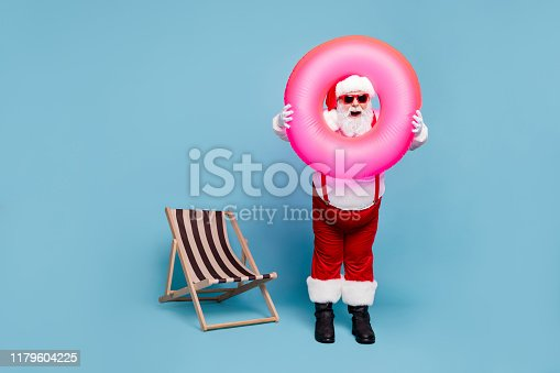 istock Full length body size view of his he nice cool comic glad cheerful cheery fat Santa carrying pink swimming circle having fun resort isolated over blue turquoise pastel color background 1179604225