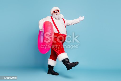 istock Full length body size view of his he nice cool stylish cheerful fat Santa walking carrying pink inflatable circle isolated on bright vivid shine vibrant blue turquoise color background 1179602978