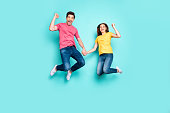Full length body size view of nice attractive winsome glad successful cheerful couple jumping up in air holding hands having fun isolated over bright vivid shine vibrant green turquoise background