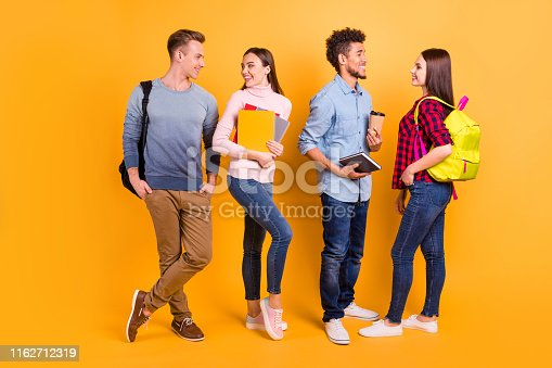 1092709104istockphoto Full length body size view of nice-looking attractive lovely friendly cheerful company buddy fellow socializing flirting communicating isolated over bright vivid shine yellow background 1162712319