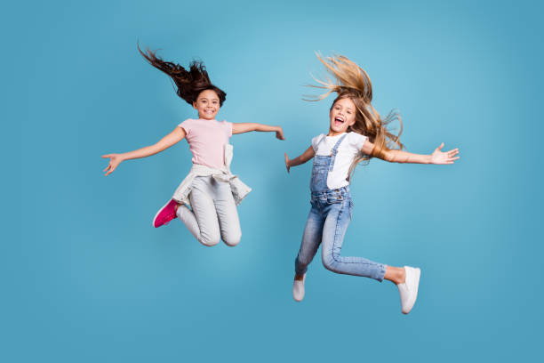 full length body size view of two people nice lovely attractive cheerful straight-haired pre-teen girls having fun day daydream yes goal achievement free time isolated on blue background - mid air stock pictures, royalty-free photos & images