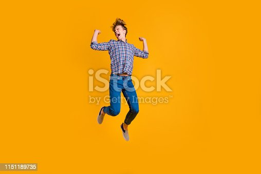 1165538246 istock photo Full length body size view portrait of his he nice attractive cheerful cheery optimistic guy in checked shirt having fun flying isolated over bright vivid shine yellow background 1151189735