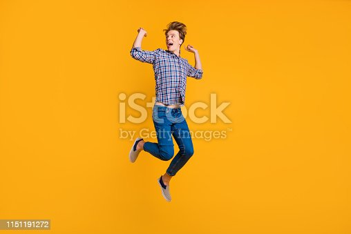 1165538246 istock photo Full length body size view portrait of his he nice-looking attractive cheerful cheery optimistic overjoyed guy in checked shirt celebrating isolated over bright vivid shine yellow background 1151191272