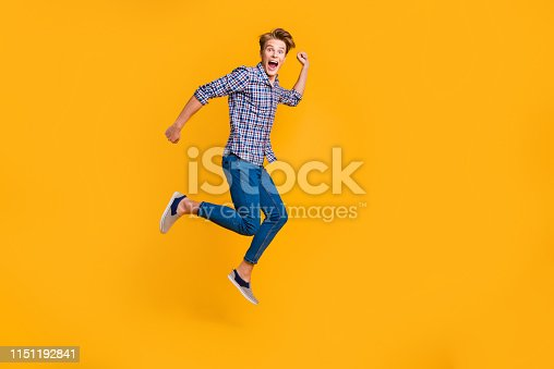 1165538246 istock photo Full length body size view portrait of nice attractive cheerful cheery optimistic guy in checked shirt having fun running fast hurry rush isolated over bright vivid shine yellow background 1151192841