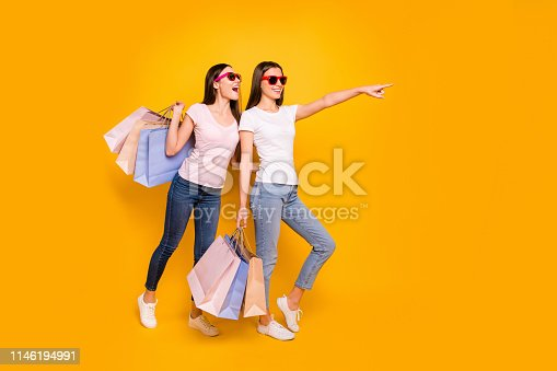 istock Full length body size view portrait of nice cute charming winsome attractive cheerful straight-haired girls carrying purchase showing far away isolated on bright vivid shine yellow background 1146194991