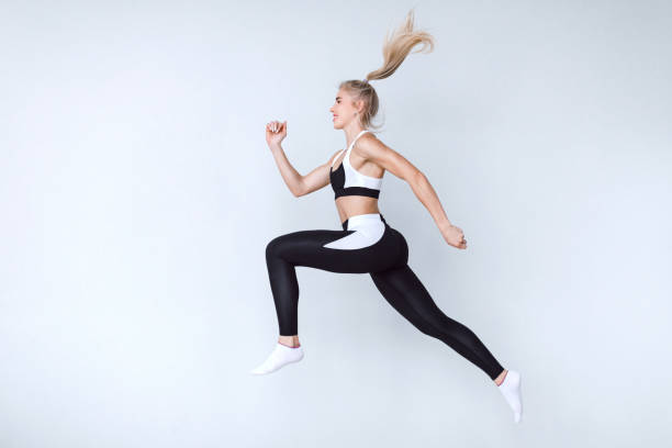 Full length fitness woman jumping agains gray background. stock photo