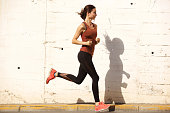 Full length side portrait of fitness woman on morning run outdoors
