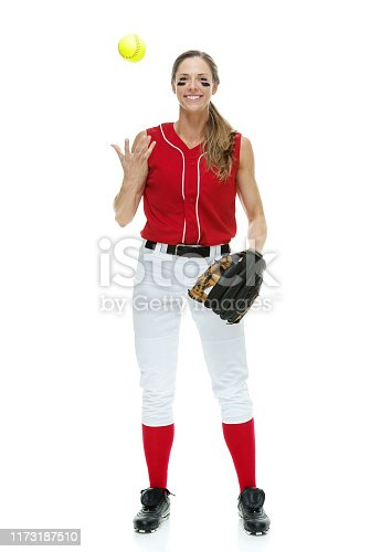 Full length / front view / looking at camera of 20-29 years old adult beautiful brown hair / long hair caucasian female / young women softball player / athlete / softball pitcher / pitcher standing in front of white background wearing baseball glove / glove who is smiling / happy / cheerful who is throwing / catching with eye black and holding softball - ball / playing softball - sport / sport