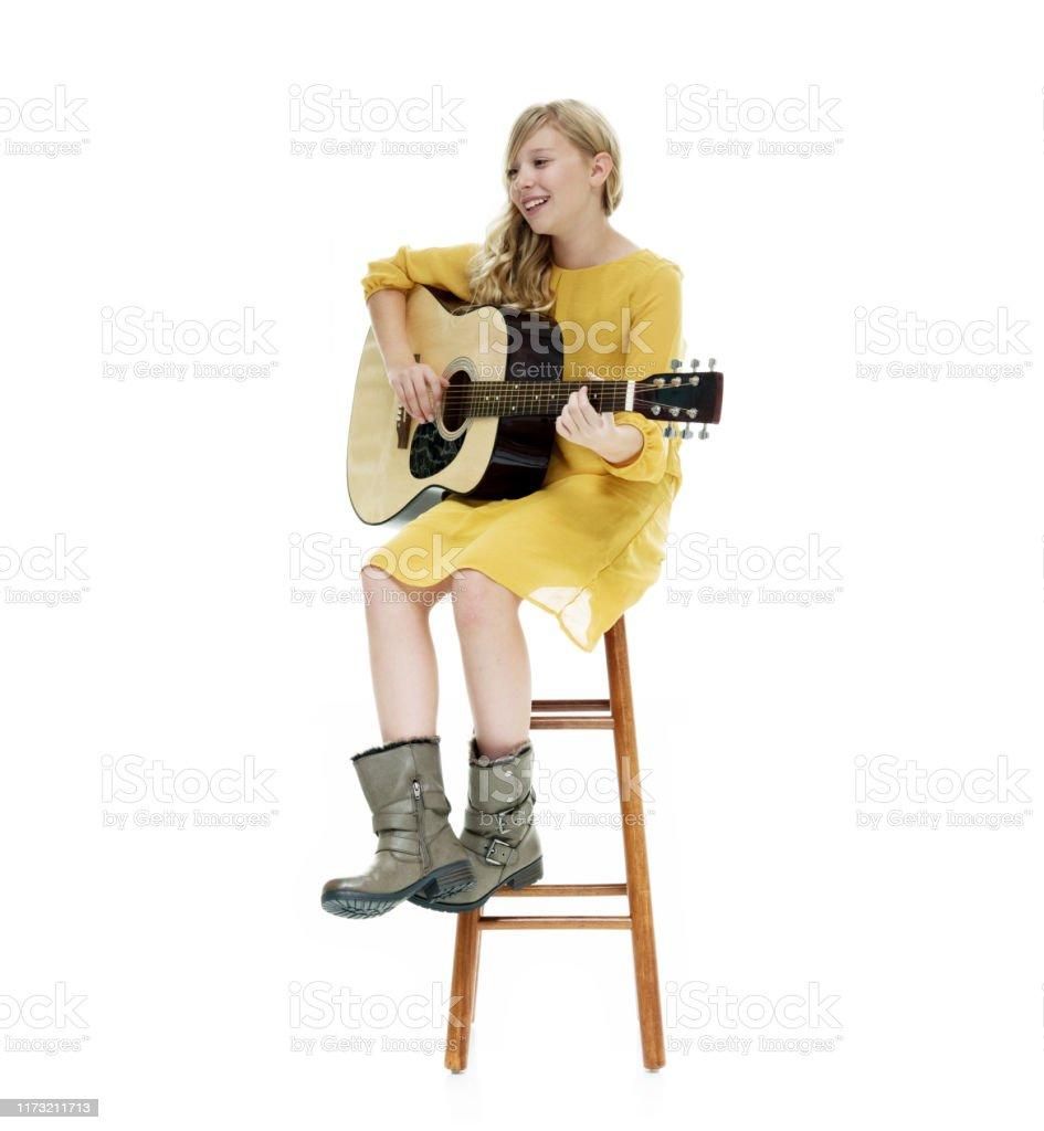 Ein junges Mädchen trägt ein weißes Kleid mit Cowboy Stiefel