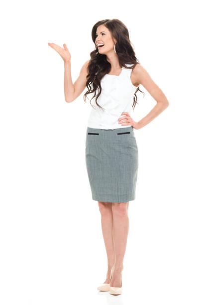 Volle Länge / Frontansicht von 20-29 Jahre alt Erwachsene schöne braune Haare / lange Haare kaukasische Frau / junge Frauen Geschäftsfrau / Geschäftsfrau / Managerin stehen vor weißem Hintergrund tragen Businesswear / Rock / formalwear / ein Anzug – Foto