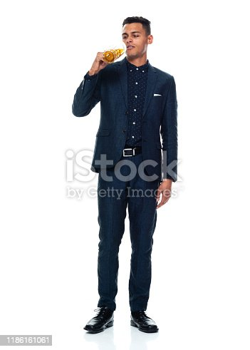 istock Full length / front view / one man only / one person of 20-29 years old adult handsome people black hair / short hair african ethnicity / african-american ethnicity male / young men businessman / business person wearing a suit who is drinking / drunk 1186161061