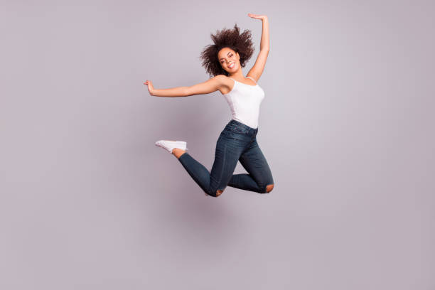 full length full size fullbody portrait of playful, crazy, childish, funny, pretty, charming positive girl jumpink with hands up, looking at camera, isolated on grey background, having fun - african youth jumping for joy stock photos and pictures