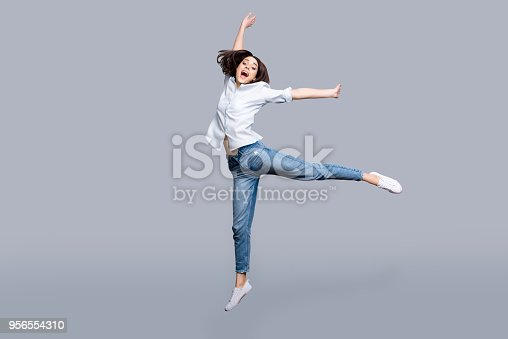 Full length, full size, fullbody portrait of pretty, charming, modern, stylish girl jumping in the air yelling with wide open mouth, celebrating successfully pass exams, isolated on grey background