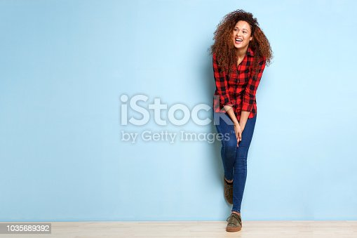 istock Full length happy woman leaning against blue background 1035689392