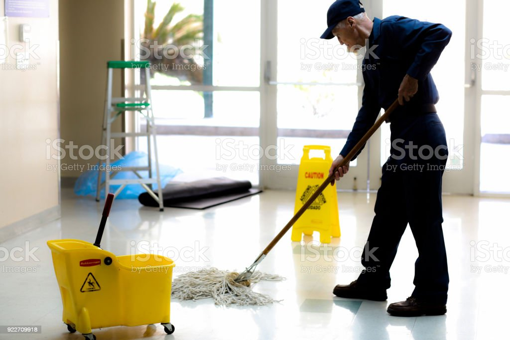 Full length image of Senior man working as a janitor in building. stock photo