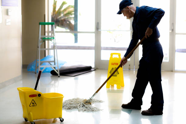 Full length image of Senior man working as a janitor in building. Here is a senior adult man working as a janitor in an office building, school or church.  He wears a uniform as he mops the entry floor.  Mop bucket and safety sign are also pictured.  He has retired and enjoys being active and still meeting people without responsibilities of the busy office demands.  Full length. cleaner stock pictures, royalty-free photos & images