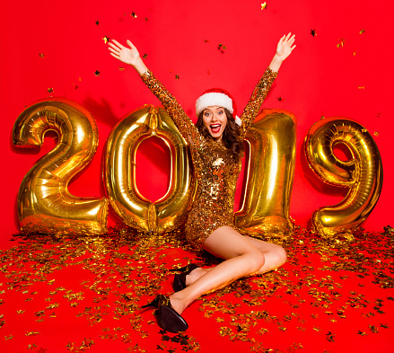 Full length, legs, body, size portrait of elegant, graceful lady in sharp, pumps, stilettos with modern curly, wave hairstyle isolated on vivid red background sit on the floor make big beaming smile